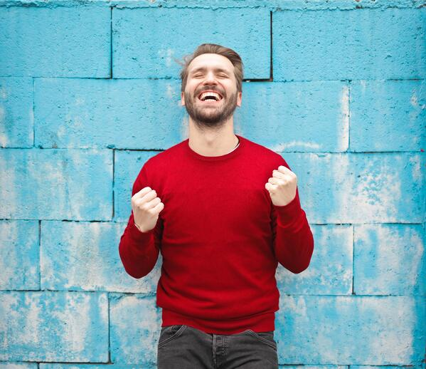 Happy person in front of blue wall