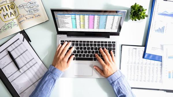Man typing data on laptop