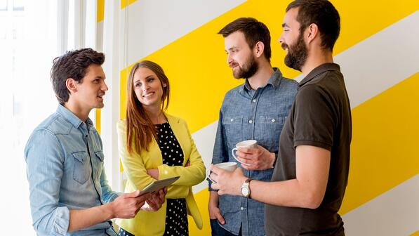 People discussing in front of yellow wall
