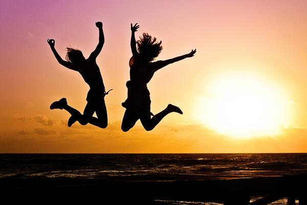 People jumping for joy in the sunset