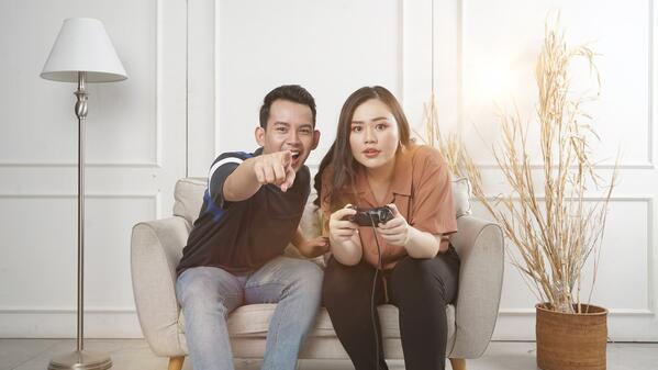 Person pointing while other person holds gaming controller