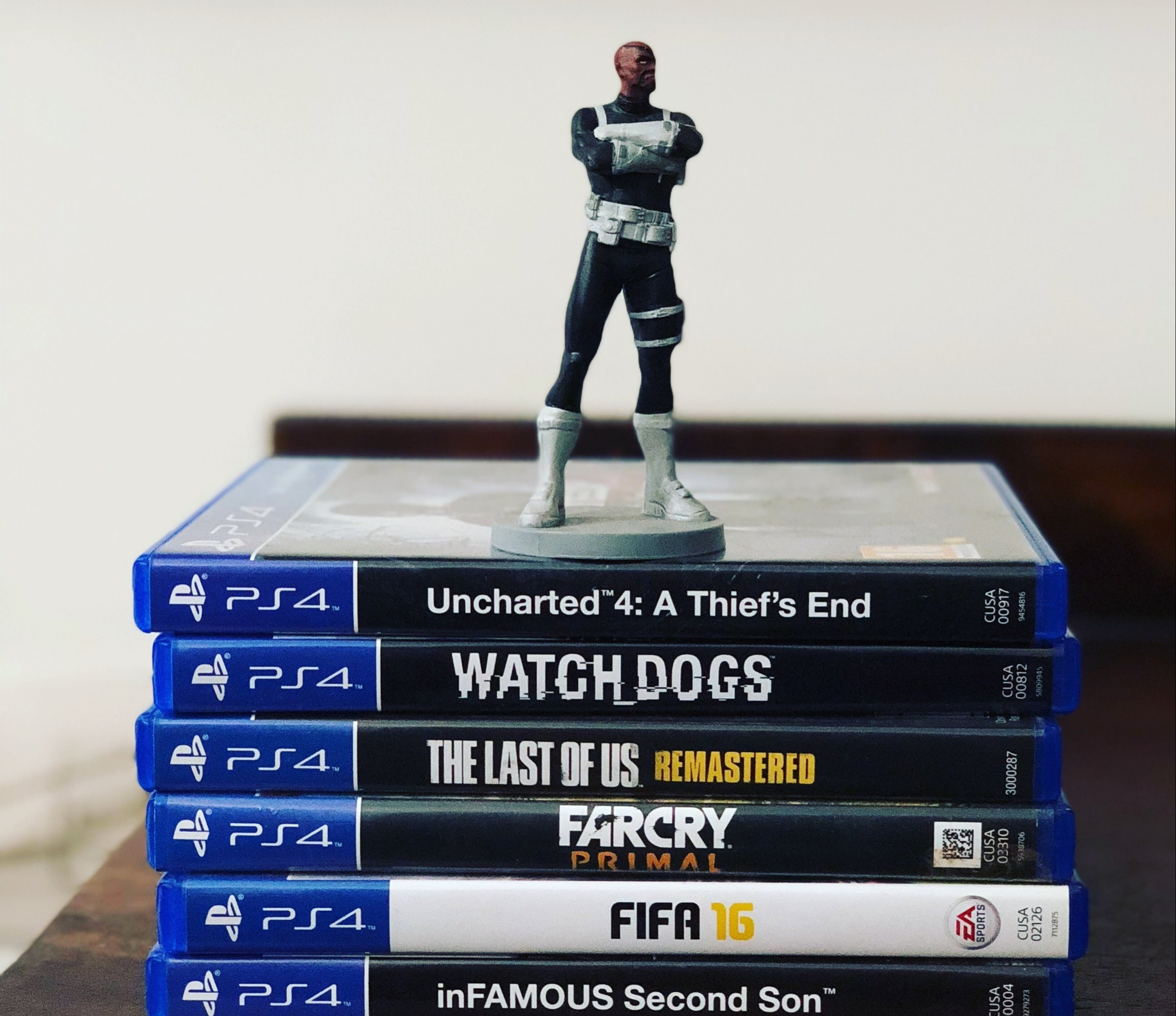 Stack of PlayStation 4 games with action figure