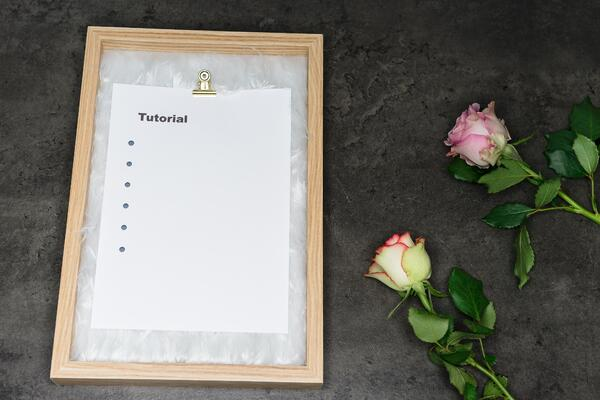 Tutorial written on white paper on clipboard with roses