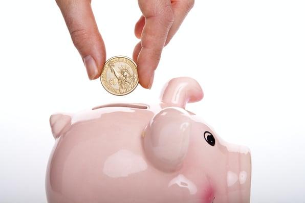 a hand that add money to a piggybank