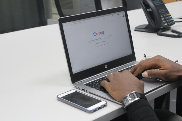 Person searching on Google using a laptop